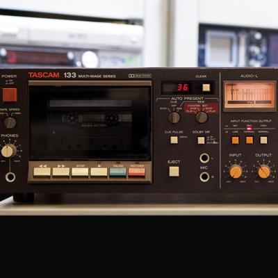 dark brown cassette deck with orange knobs and amber lit VDU meter