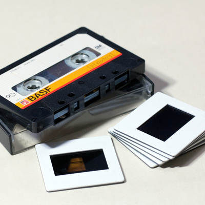 BASF cassette tape resting on plastic box with stack of 6 white plastic-framed colour transparency slides
